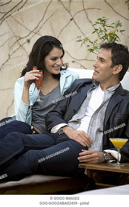 Couple having drinks in lawn chair