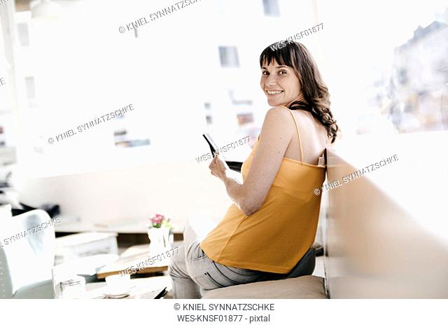 Woman sitting in cafe, using tablet pc