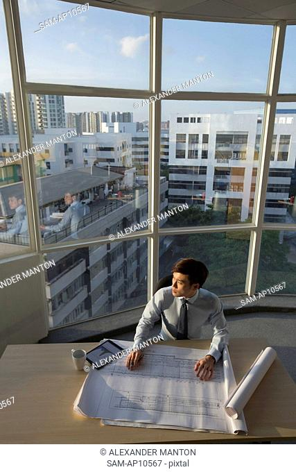 Singapore, Architect sitting at desk with architectural plans and digital tablet