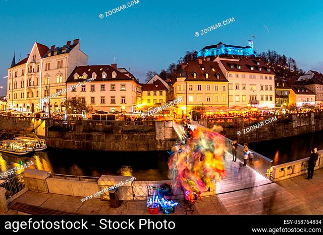 View of lively river Ljubljanica bank in old city center decorated with Christmas lights at dusk. Old medieval Ljubljana cstle on the hill obove the city