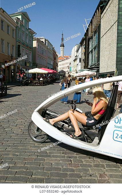 Modern bicycle taxi waiting for customers with Town Hall Raekoda in the background in Old Town. Tallinn. Estonia