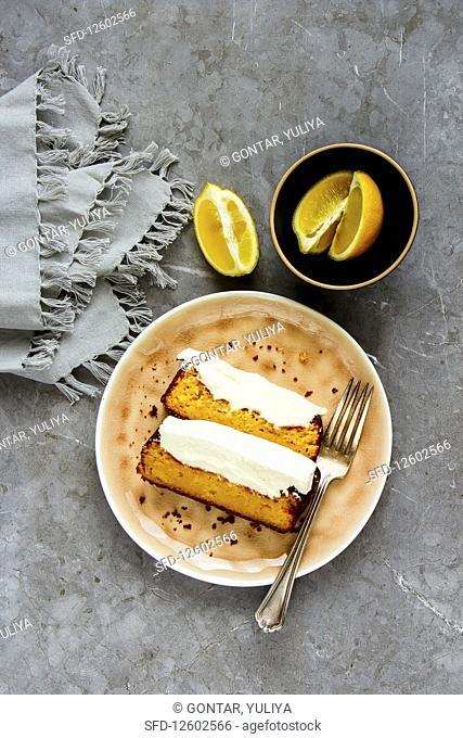 Flat-lay of sliced freshly baked lemon cake dessert with mascarpone cream in plate over grey concrete background
