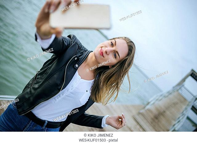 Portrait of smiling young woman taking selfie on boardwalk