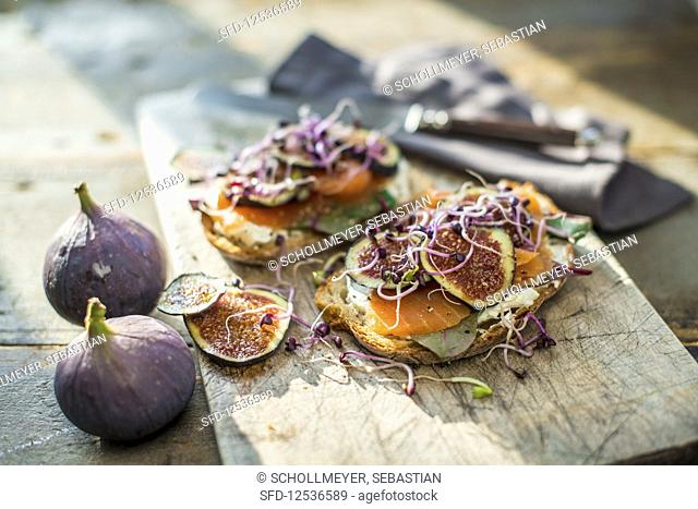 Salmon sandwiches with figs and sprouts on a wooden board