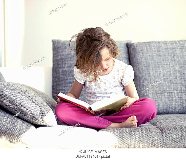Young girl sitting on sofa, reading
