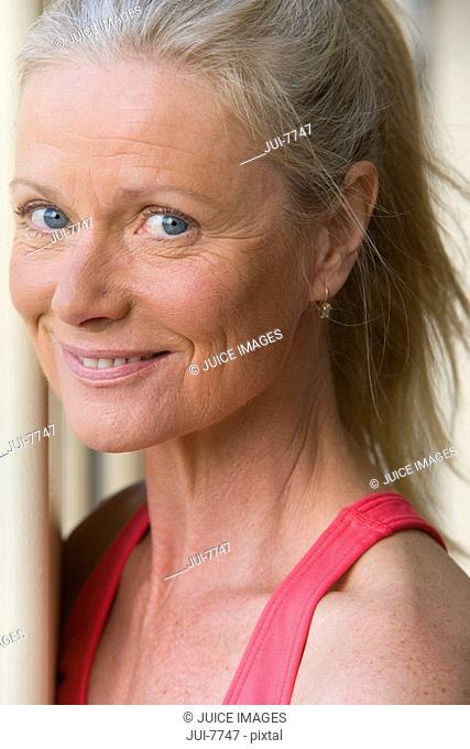 Active senior woman wearing pink sports vest, smiling, close-up, side view, portrait