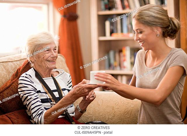 Care assistant handing coffee cup to senior woman