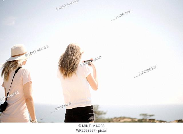 Woman and teenage girl with long blond hair standing outdoors, holding up a mobile phone, taking a picture