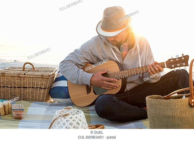 Young man playing guitar on sunlit beach, Cape Town, Western Cape, South Africa