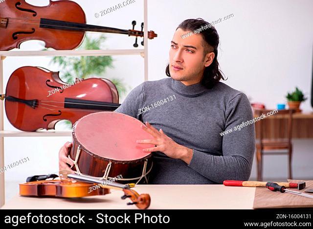 Young male repairman repairing drum in workshop