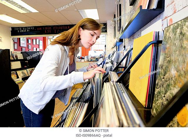 Young woman looking at stacked vinyl records in record store