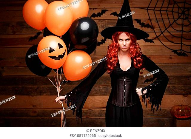 Halloween Witch Concept - Beautiful caucasian woman in witch costumes celebrating Halloween posing with posing with orange and black balloon over bats and...
