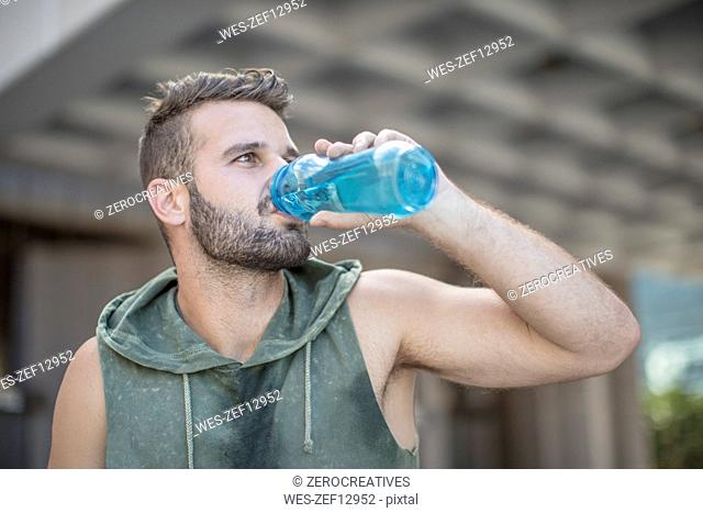 Athlete taking a break in the city drinking water from bottle