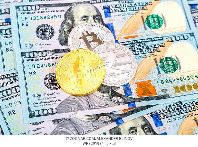 Gold and silver coins of cryptocurrency lying over one hundred american dollar banknotes. Business concept