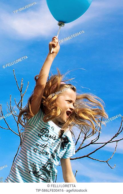 Female child releasing blue balloon