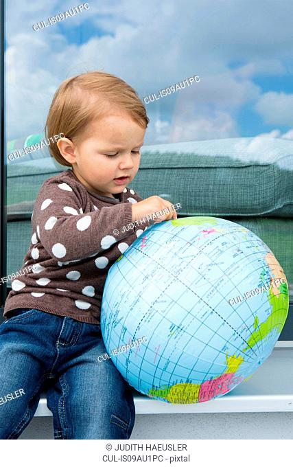 Female toddler playing with inflatable globe on windowsill
