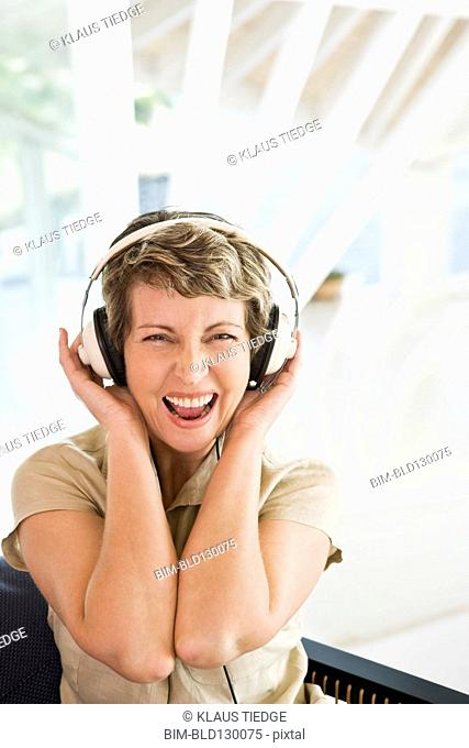Woman listening to headphones on stairs