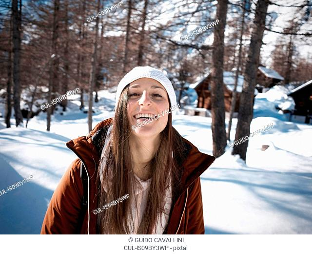 Young woman in knit hat in snow covered forest, portrait, Alpe Ciamporino, Piemonte, Italy