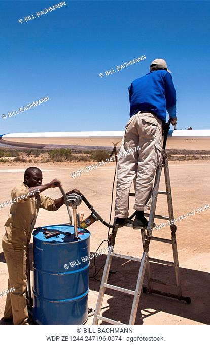 Namibia Namib Desert refueling plane in the Hartmann Berge Marienflub sand remote landing strip with workers pumping manually fuel gas