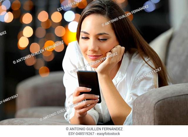 Girl reading phone messages in the night lying on a couch in the living room at home