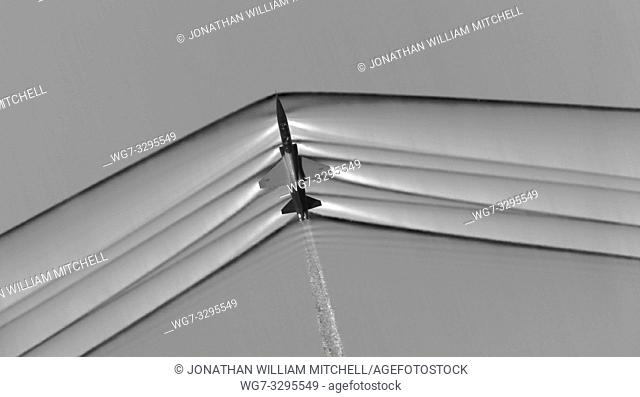 USA -- This schlieren image dramatically displays the shock wave of a supersonic jet flying over the Mojave Desert. Researchers used NASA-developed image...
