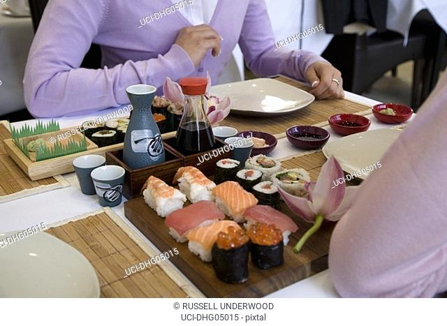 Sushi on table between two people