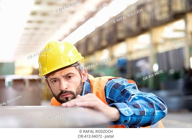 Serious steel worker examining steel in factory