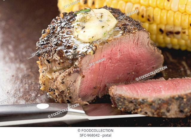 Peppered steak with herb butter and corn on the cob