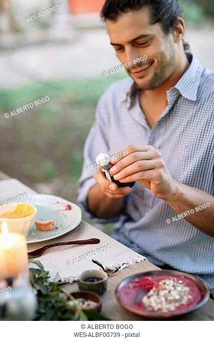 Man opening a bottle of sparkling wine at garden table