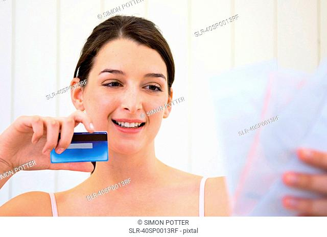 Woman with credit card and bills
