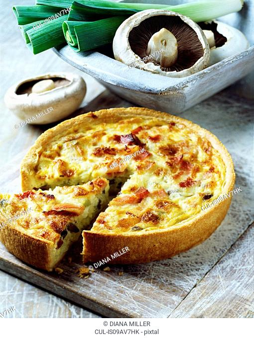 Ham, mushroom and leek quiche on white washed chopping board