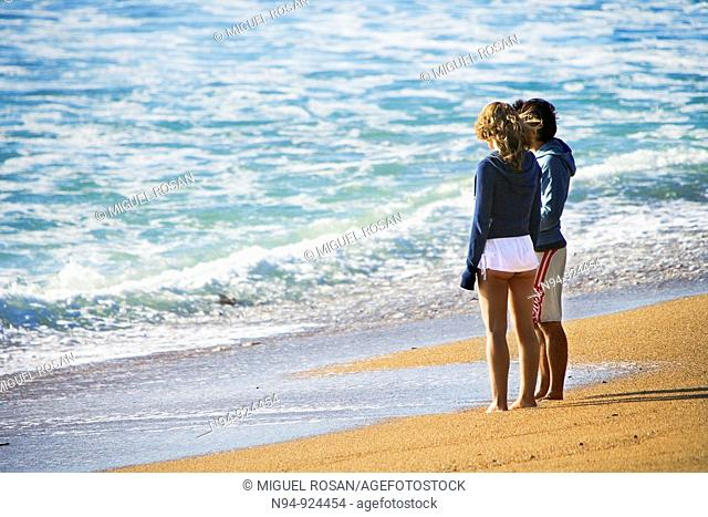 Mature young boy and girl relaxed, watching the sea