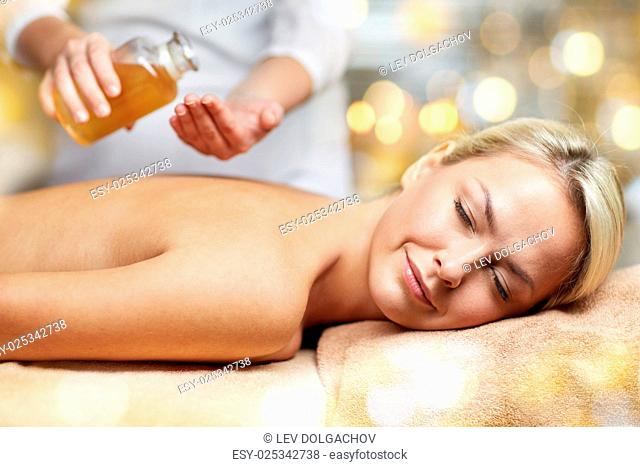 people, beauty, spa, healthy lifestyle and relaxation concept - close up of beautiful young woman lying with closed eyes on massage table and therapist holding...