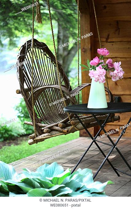 Country setting with Adirondack porch swing and a pitcher of peonies flowers