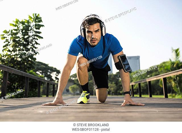 Runner training start position on street in urban park, wearing headphones