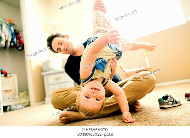 Father dressing young son, father holding son upside down