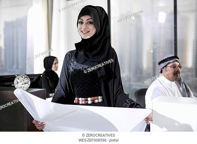 Middle Eastern businesswoman in office holding plan