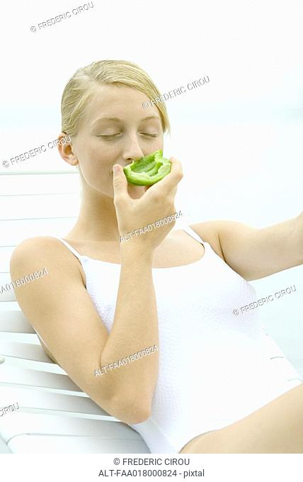 Teenage girl wearing bathing suit, sitting in lounge chair, smelling piece of green pepper