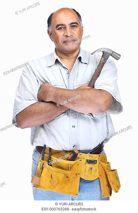 Confident serious senior handyman wearing a tool belt with hammer in hand