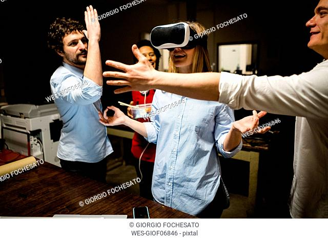 Colleagues with woman wearing VR glasses in office