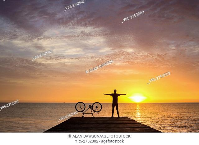 A mountain biker stretches as he watches the sun rise over the North sea on a calm and tranquil morning at Seaton Carew, north east England, United Kingdom