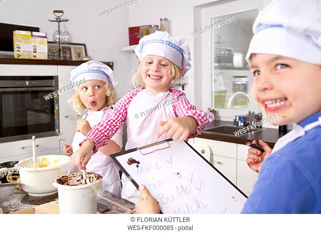 Germany, Girls and boy baking dough with recipe, smiling