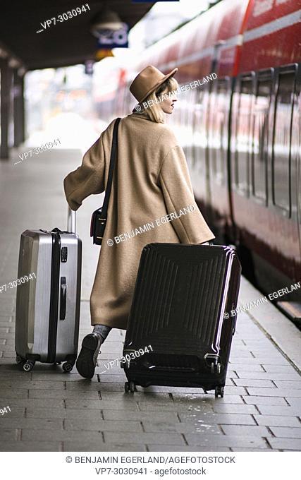 Fashion blogger Esra Eren aka @nachgestern waiting for train, with trolley bags. At Munich central station, Germany