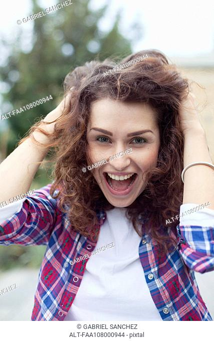 Carefree young woman laughing outdoors, portrait