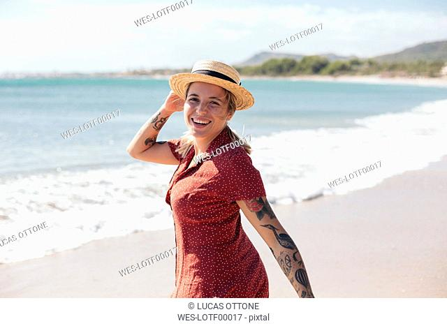 Spain, Mallorca, portrait of happy young woman with tattoos on the beach