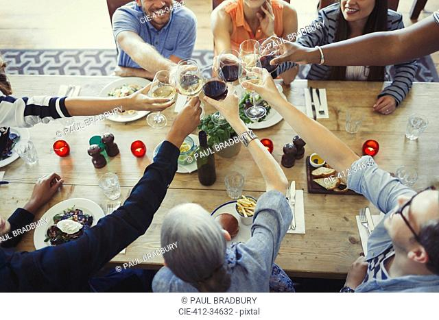Overhead view friends toasting wine glasses at restaurant table