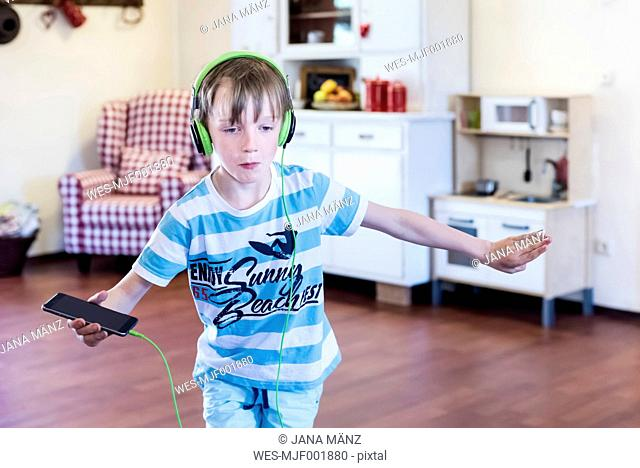 Boy with cell phone and headphones dancing
