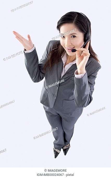 Young business woman wearing headphone and smiling at the camera