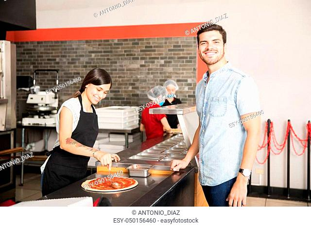 Happy customer looking at camera while woman chef in black apron preparing pizza in kitchen counter
