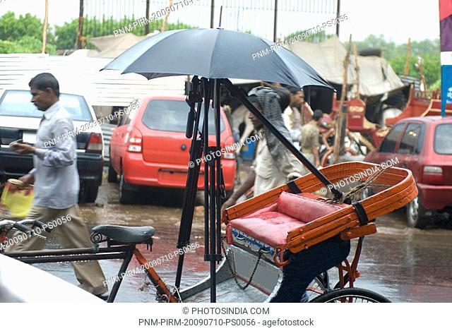 Tripod sheltered by an umbrella on a rickshaw, New Delhi, India